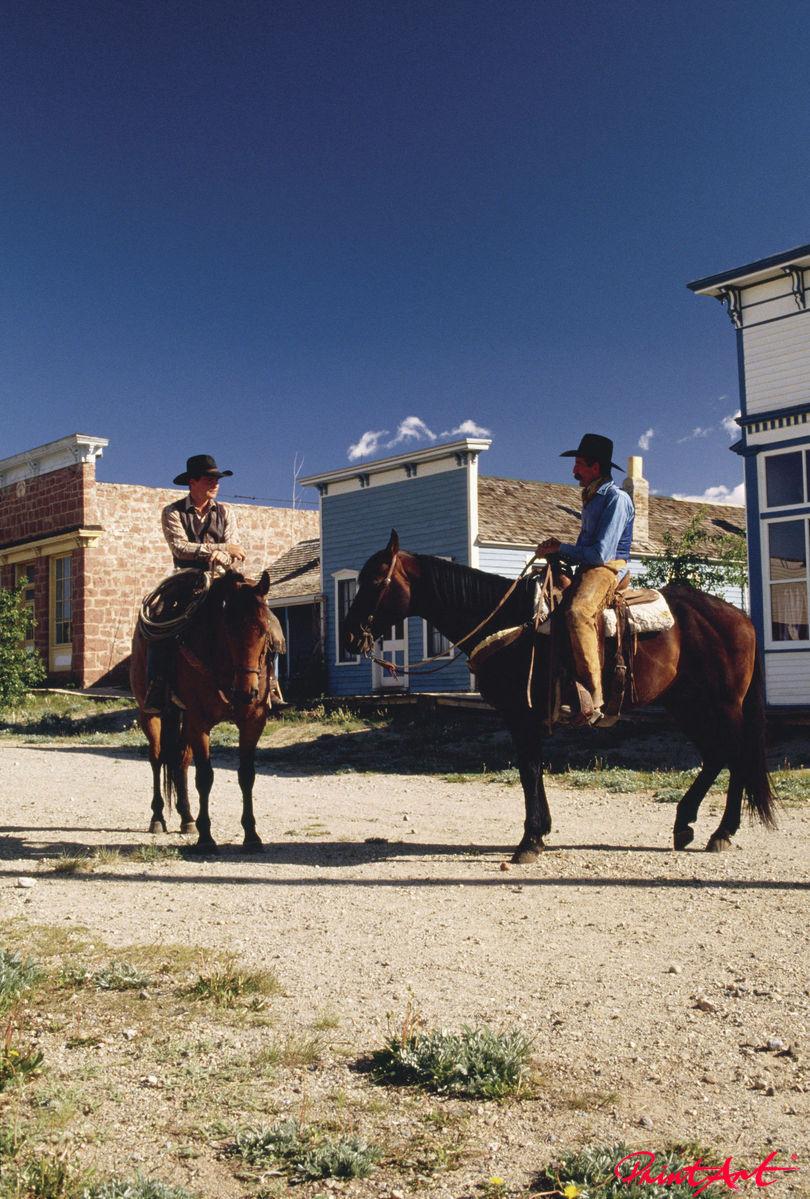 Cowboys vor Westernstadt Pferde
